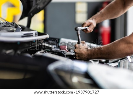 Caucasian male mechanic repairs car in garage. Car maintenance and auto service garage concept. Closeup hand and spanner. Royalty-Free Stock Photo #1937901727