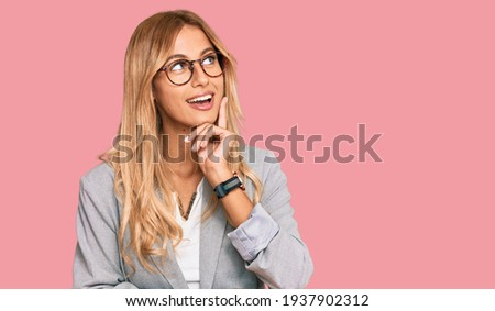Beautiful blonde young woman wearing business clothes with hand on chin thinking about question, pensive expression. smiling and thoughtful face. doubt concept.  Royalty-Free Stock Photo #1937902312
