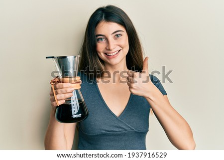 Young caucasian woman holding coffee maker with filter smiling happy and positive, thumb up doing excellent and approval sign