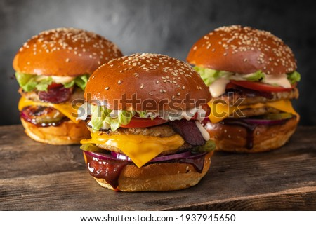 Three yummy juicy hamburgers with double cutlet and cheese on a wooden table. Grilled chicken burger. Royalty-Free Stock Photo #1937945650