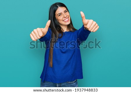 Young hispanic woman wearing casual clothes approving doing positive gesture with hand, thumbs up smiling and happy for success. winner gesture.  Royalty-Free Stock Photo #1937948833