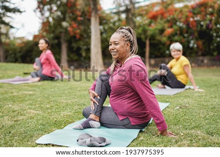 Multiracial women doing yoga exercise with social distance for coronavirus outbreak at park outdoor - Healthy lifestyle and sport concept Royalty-Free Stock Photo #1937975395