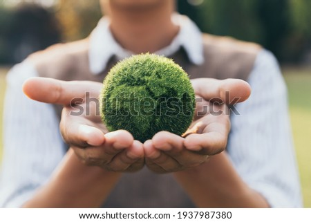 Asian teenager showing earth on hand, ecology and environment sustainable concept. Royalty-Free Stock Photo #1937987380