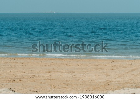 View of the beach at Beyt Dwarka in Gujarat, India. Sea waves crashing on the shore of the beach. Holiday relaxation concept. Sea waves at the shore, Relaxation at the beach. Summer travel background. Royalty-Free Stock Photo #1938016000