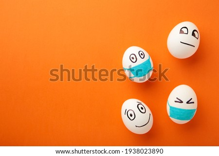 White Easter eggs in protective medical mask and two egg without mask on orange background. Easter on quarantine concept with place for text. Stop VIRUS COVID-19. Copy space.