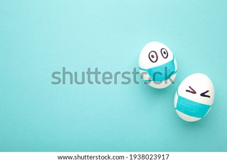 White Easter eggs in protective medical mask on blue background. Easter on quarantine concept with place for text. Stop VIRUS COVID-19. Copy space. Egg in mask. Top view