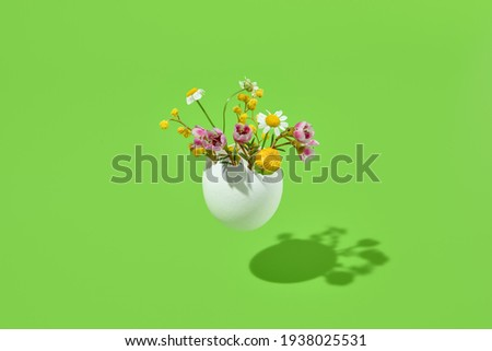White egg and spring flowers bouquet. Easter minimal gift on green background. Happy easter, spring or summer, food conceptual layout Royalty-Free Stock Photo #1938025531