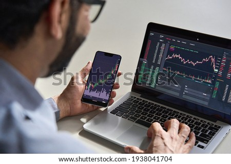 Business man trader investor analyst using mobile phone app analytics for cryptocurrency financial market analysis, trading data index chart graph on smartphone and laptop screen. Over shoulder view Royalty-Free Stock Photo #1938041704