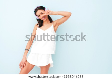 Beautiful smiling woman dressed in white pajamas.Sexy carefree model listening music in wireless headphones.Positive female posing and dancing near light blue wall in studio.Shows peace sign