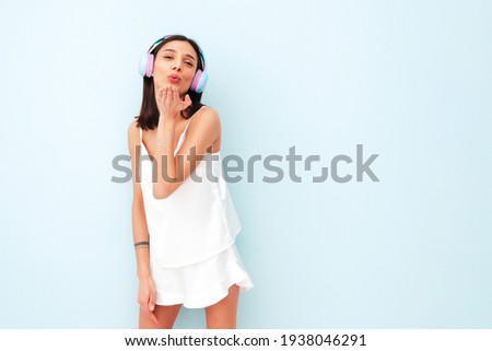 Beautiful smiling woman dressed in white pajamas.Sexy carefree model listening music in wireless headphones.Positive female posing and dancing near light blue wall in studio.Gives air kiss