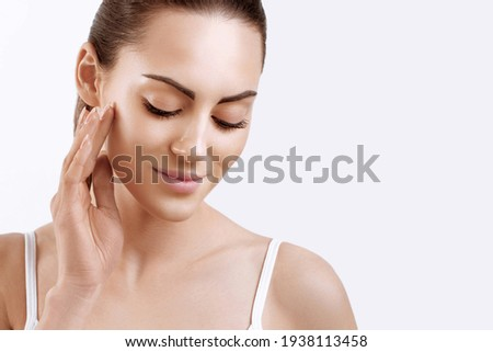 Skin care. Woman with beauty face touching healthy facial skin portrait. Beautiful smiling girl model with natural makeup touching her skin  Royalty-Free Stock Photo #1938113458