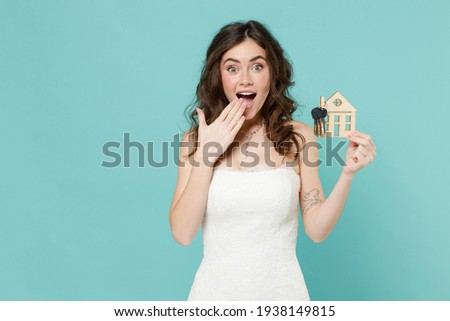 Shocked bride young woman 20s in white wedding dress hold house bunch of apartment keys cover mouth with hand isolated on blue turquoise background studio portrait. Ceremony celebration party concept Royalty-Free Stock Photo #1938149815