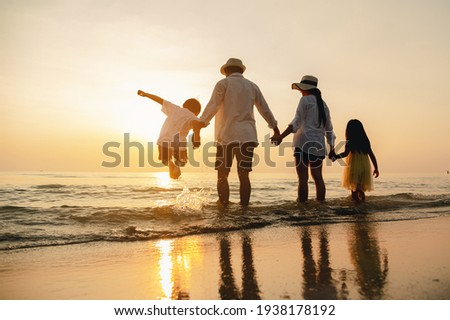 Happy asian family jumping together on the beach in holiday. Silhouette of the family holding hands enjoying the sunset on the  beach.Happy family travel and vacations concept.  Royalty-Free Stock Photo #1938178192