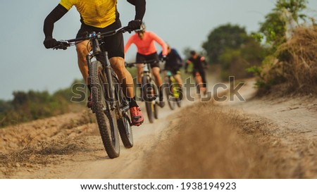 Group of Asian cyclists, they cycle through rural and forest roads. Royalty-Free Stock Photo #1938194923