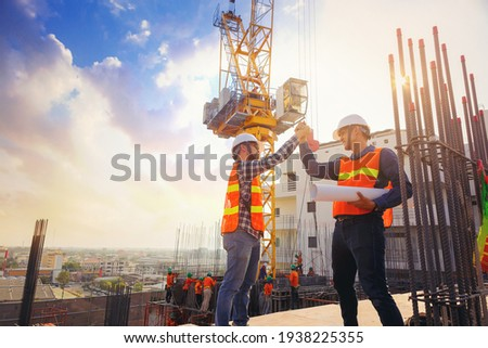 Architect and engineer construction workers shaking hands while working at outdoors construction site. Building construction collaboration concept Royalty-Free Stock Photo #1938225355