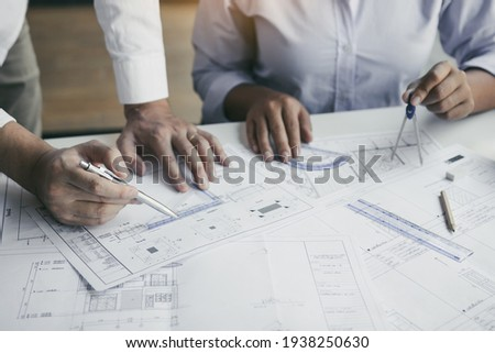 The partnership engineering man or co-workers working on a project and discussing together with looking at blueprint paperwork. Royalty-Free Stock Photo #1938250630