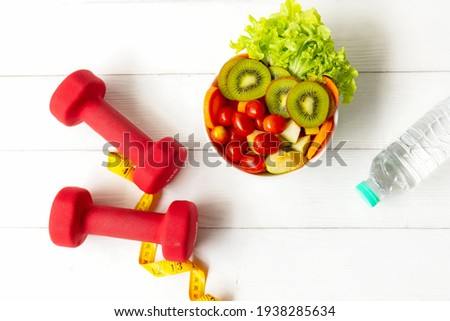 Diet Healthy food and lifestyle health concept. Sport exercise equipment workoutandgym background with nutrition detox salad for fitness style. Health care Concept Royalty-Free Stock Photo #1938285634