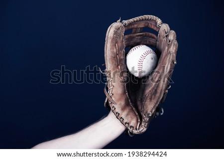 Close up image of an old used baseball and baseball glove. Royalty-Free Stock Photo #1938294424