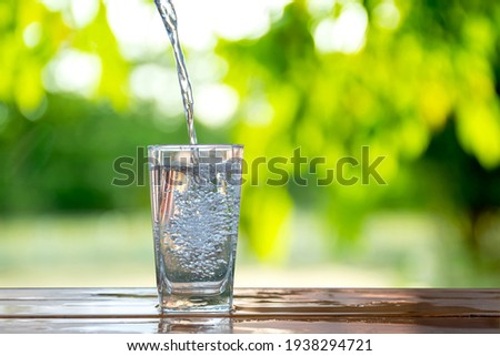 Water flows into a glass placed on a wooden bar. Royalty-Free Stock Photo #1938294721