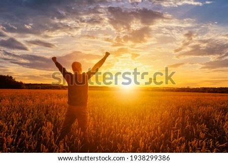 Silhouette of a man raise his hands up to sunset or sunrise on the field with young rye or wheat in the summer with a cloudy sky background.  Royalty-Free Stock Photo #1938299386