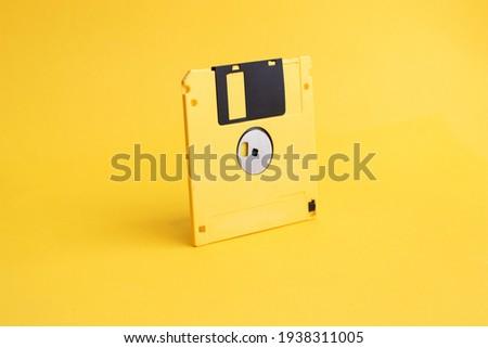 Yellow floppy disk on yellow background.
