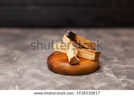 Scattered sticks of Palo Santo tree on grey background. Organic holy tree incense from Latin America. Color photo close-up of natural frankincense. It helps to enhance clarity and concentration