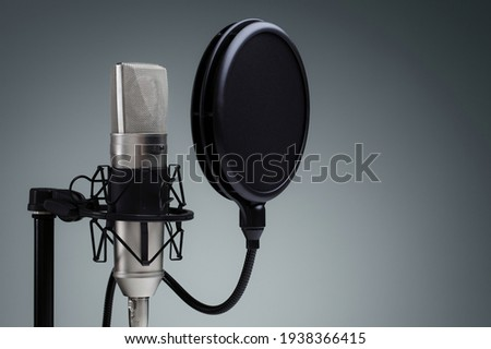 Studio condenser mic on mic-stand with popup filter isolated in a grey background.