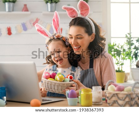 Mother and her daughter painting eggs. Happy family preparing for Easter. Cute little child girl wearing bunny ears. Royalty-Free Stock Photo #1938367393