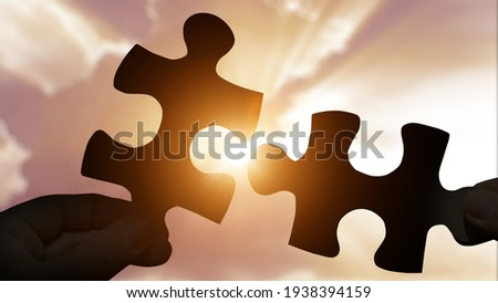 Puzzle pieces connecting with hands on sunset background Royalty-Free Stock Photo #1938394159