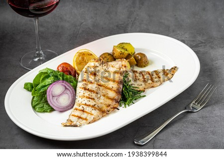 Grilled sea bass fillet with salad and potatoes on stone table Royalty-Free Stock Photo #1938399844