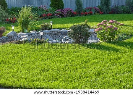 Decorative stones and pebble gravel in landscaping. Lush green lawn and shrubbery in the backyard. Royalty-Free Stock Photo #1938414469