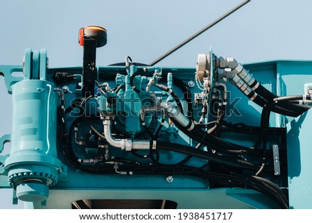 Hydraulic crane engine.The control system of the crane engine.Lifting hydraulic Department on the truck crane.The hydraulic system of the engine.hydraulic hoses on the crane.autoparts. Royalty-Free Stock Photo #1938451717