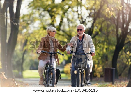 Cheerful active senior couple with bicycle in public park together having fun. Perfect activities for elderly people. Happy mature couple riding bicycles in park Royalty-Free Stock Photo #1938456115