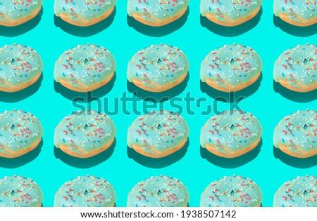 Closeup Trendy sunlight Summer pattern made with pink doughnut on bright light blue background. Minimal summer concept.