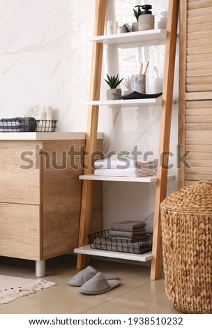 Soft towels and different toiletries on decorative ladder in bathroom. Interior design Royalty-Free Stock Photo #1938510232