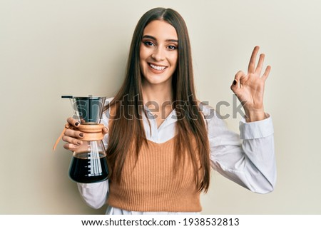Beautiful brunette young woman holding soluble coffee maker doing ok sign with fingers, smiling friendly gesturing excellent symbol