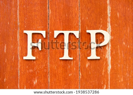 Alphabet letter in word FTP (Abbreviation of File Transfer Protocol) on old red color wood plate background