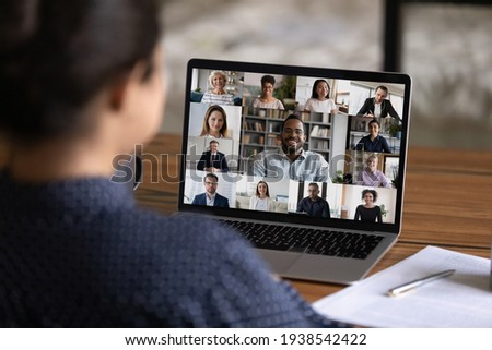 Over shoulder view of female worker have webcam digital virtual conference with diverse multiethnic colleagues. Woman speak talk on video call with multiracial businesspeople. Online meeting concept. Royalty-Free Stock Photo #1938542422