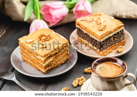 Piece of homemade poppy seed cake and a slice of layered honey cake on the wooden table. Festive set with pastry desserts, cup of coffee and tulip flowers on the background Royalty-Free Stock Photo #1938543220