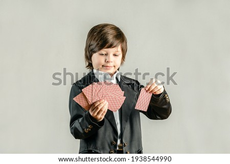 Young six year old boy wearing black suit and showing playing cards trick during illusionist performance. Pocker player Royalty-Free Stock Photo #1938544990