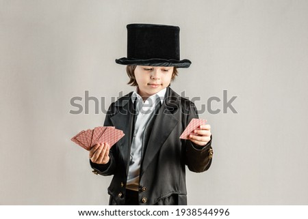 Young six year old boy wearing black suit and showing playing cards trick during illusionist performance. Cosplay, Retro party or Halloween costume concept. Royalty-Free Stock Photo #1938544996