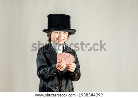 Young six year old boy wearing black suit and showing playing cards trick during illusionist performance. Cosplay, Retro party or Halloween costume concept. Royalty-Free Stock Photo #1938544999