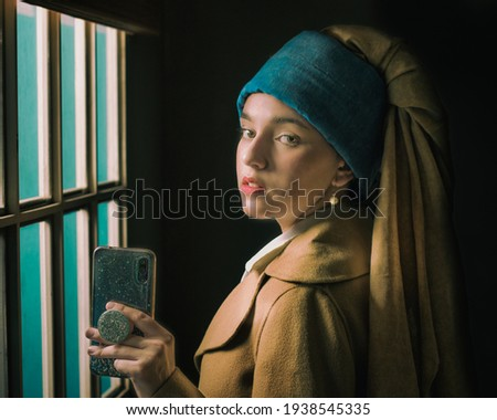 """Photo """"The Girl With a Pearl Earring"""", with girl posing and dressing like Veermer's painting holding a cell phone"""