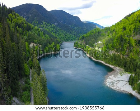 Aerial panorama of Petrimanu Lake and a gravel road winding along its shores. Spring time, the trees are blooming. A spring flows into the lake on the right shore. Carpathia, Romania. Royalty-Free Stock Photo #1938555766