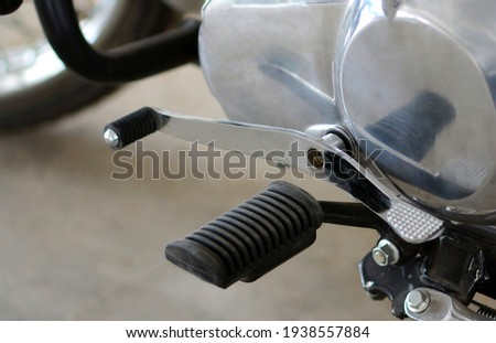 Close-up  view of Gear switch mechanism of a motor bike and foot rest                                       Royalty-Free Stock Photo #1938557884