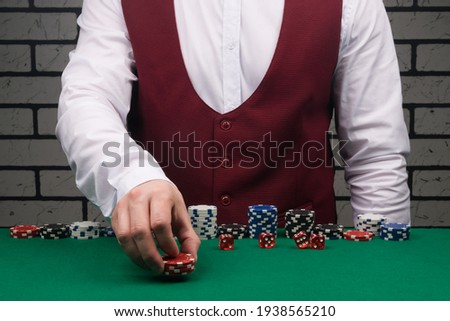 the croupier at the green poker table bets with red chips