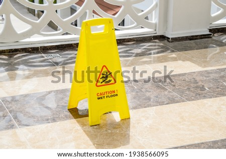 Yellow warning sign Caution Wet Floor on a marble floor in a public area. Preventing injuries to hotel guests during wet cleaning of halls and public places. Royalty-Free Stock Photo #1938566095