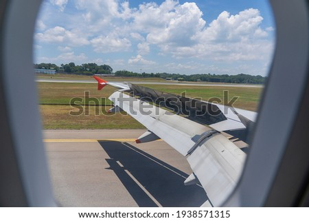 An airplane window view of wing and flaps after landing. Landing aircraft at the airport. Braking of the aircraft on the runway, wing of the plane is in working order. View from window. Close up shot Royalty-Free Stock Photo #1938571315