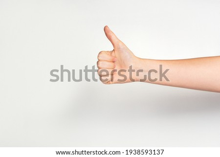Woman's hand gesturing thumbs up showing good or ok on light grey background. Royalty-Free Stock Photo #1938593137
