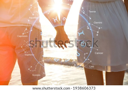 Hands of a couple with love compatibility between zodiac signs Royalty-Free Stock Photo #1938606373